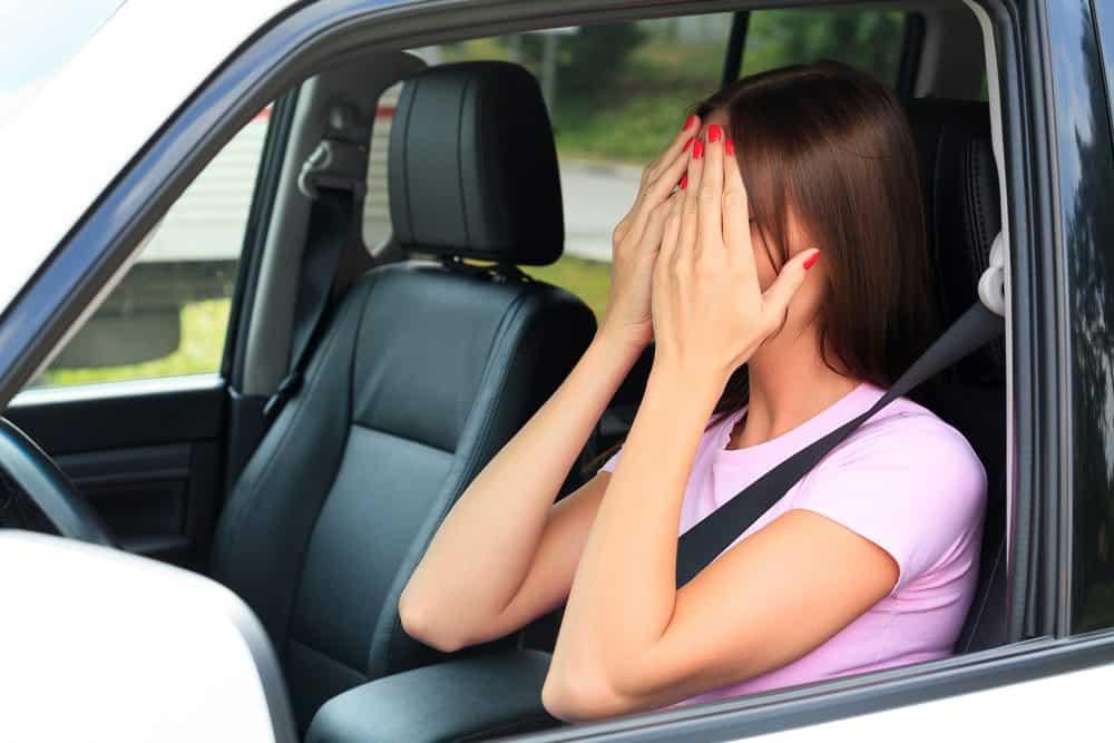 mulher dentro de um carro cobrindo o rosto com as duas mãos preocupada com a nova lei de trânsito