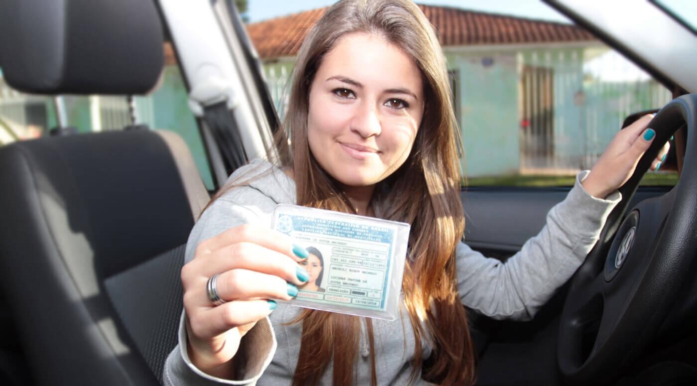 mulher branca dentro de um carro segurando a cnh renovada